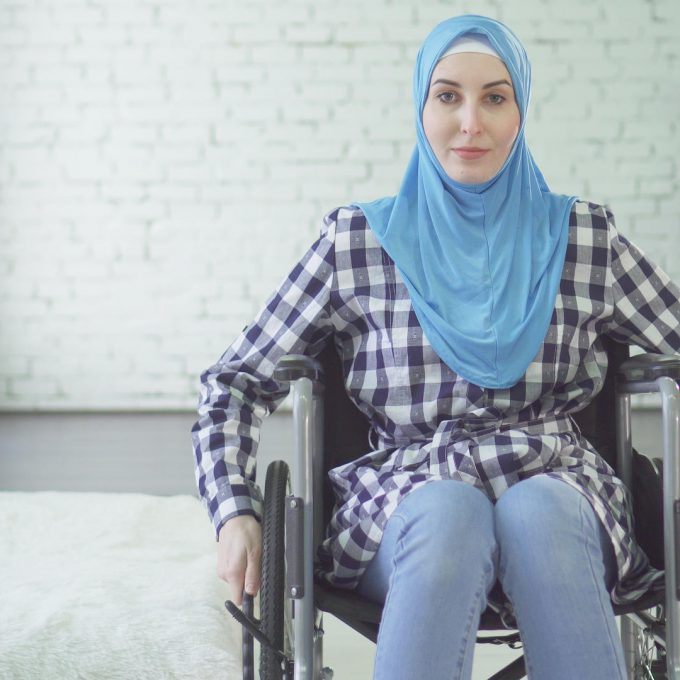 Beautiful young woman in hijab disabled person in wheelchair in her apartment